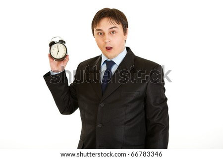 Shocked businessman holding alarm clock. Lost time concept isolated on white - stock photo
