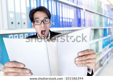 Shocked businessman reading a book shot in the office