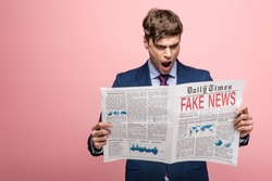 shocked businessman reading newspaper with fake news on pink background