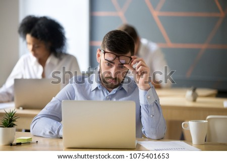 Shocked businessman stunned by online news raising glasses to look at laptop in coworking office, stock broker surprised by market changes watching video or reading information on computer screen