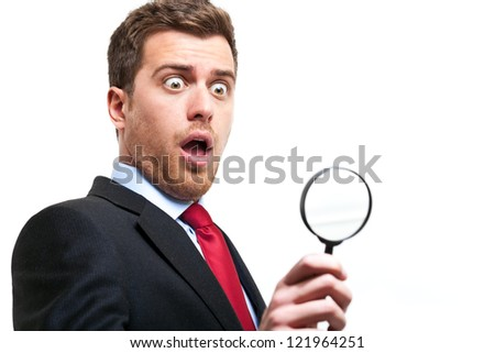 Shocked businessman using a magnifying lens