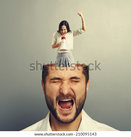 shocked businessman with open head. angry young businesswoman standing into the head, looking at the man and screaming with megaphone. photo over grey background