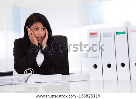 Shocked Businesswoman Looking At Folder In Office