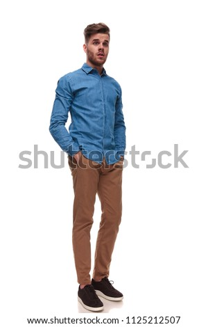 shocked casual man standing with hands in pockets on white background looks to side, full length picture #1125212507