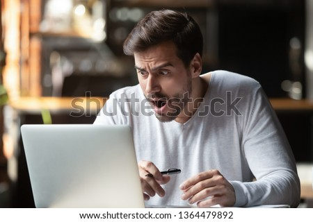 Shocked caucasian man millennial businessman sitting alone at table looking at laptop screen feels surprised and worried opening mouth making big eyes. Unbelievable things awful news problems concept