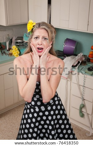 Shocked Caucasian woman in messy retro-style kitchen with hands on face