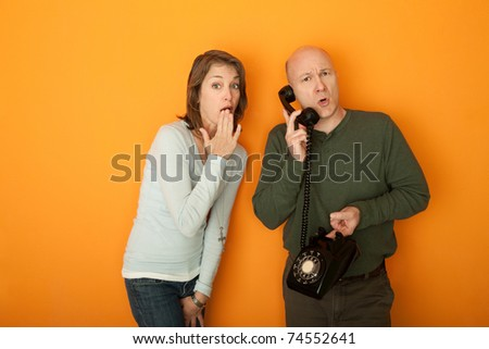 Shocked Caucasian woman with hand on mouth listening to a telephone conversation