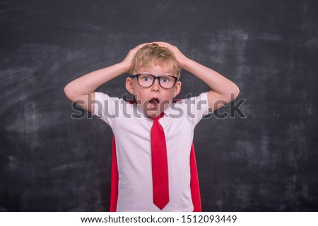 Shocked child boy with hands on head, School boy in glasses with open mouth. Shocking news.
