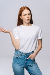Shocked confused young woman wearing T-shirt and denim pants with opened mouth and raised hands on isolated white background. Pretty lady model with red hair emotionally showing facial expressions.