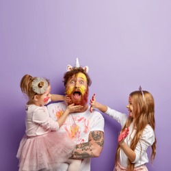 Shocked dad spends free time with daughters, dressed in unicorn costume, two children touch his face and dirty with colourful paints, surprised to be in colors. Father and little girls have fun indoor