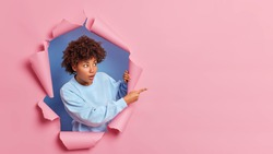 Shocked dark skinned woman with Afro hair advertises wonderful item has stunned face expression looks with great wonder at right side wears blue sweater poses in ripped paper hole. Omg look there