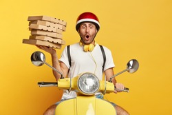 Shocked delivery boy astonished to see accident at road, surprised to come on wrong address, carries pile of cardboard pizza boxes, confused customers, poses on fast scooter, isolated on yellow wall
