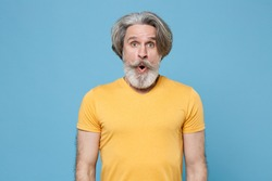 Shocked elderly gray-haired mustache bearded man in casual yellow t-shirt posing isolated on blue background studio portrait. People emotions lifestyle concept. Mock up copy space. Keeping mouth open