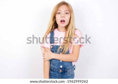 Shocked embarrassed beautiful caucasian little girl wearing jeans overall over white background keeps mouth widely opened. Hears unbelievable novelty stares in stupor Foto d'archivio ©