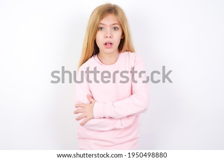 Shocked embarrassed beautiful caucasian little girl wearing pink sweater keeps mouth widely opened. Hears unbelievable novelty stares in stupor Foto d'archivio ©