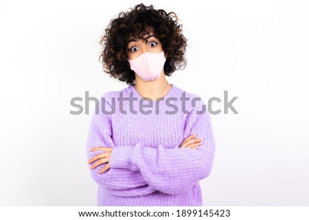 Shocked embarrassed young beautiful caucasian woman wearing medical mask standing against white wall, keeps mouth widely opened. Hears unbelievable novelty stares in stupor Foto d'archivio ©