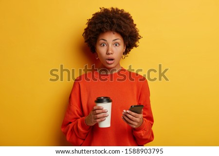 Shocked ethnic woman gets shocking message on smartphone, drinks coffee from paper cup, checks newsfeed, keeps mouth opened, realizes something went wrong, afraids of consequences, isolated on yellow