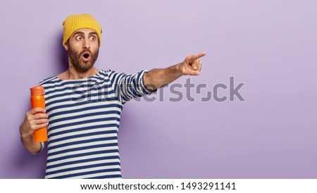 Shocked European man points into distance, notices something amazing, holds orange thermos with hot coffee, wears stylish hat and striped sweater, poses against violet wall, blank space for your text #1493291141