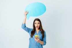 Shocked excited young woman using her mobile phone holding chat bubble above her head with blank space for text while standing on white studio background