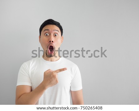 Photo of  Shocked face of Asian man in white shirt on grey background.