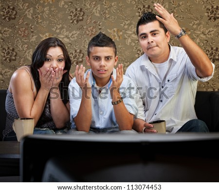 Shocked family of three watching television with hands in the air - stock photo