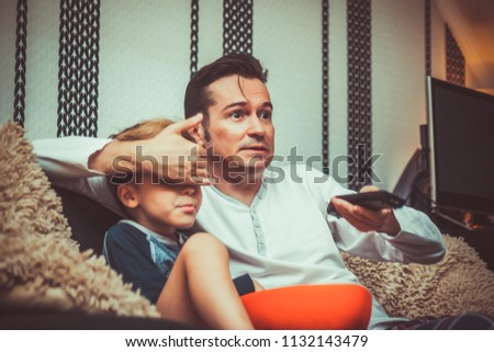 Shocked father covering son's eyes and changing channel while watching inappropriate television content at home.