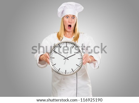 Shocked Female Chef Holding Clock against a grey background