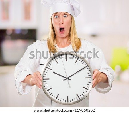 Shocked Female Chef Holding Clock in a kitchen, indoor