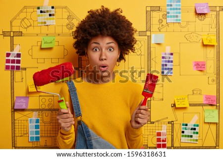 Shocked female painter stands with repair tools, prepares for room painting, stunned there is no paint, wears yellow jumper, poses against interior design sketch with sticky notes. Making reform