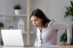Shocked female sitting at desk looking at laptop screen rounding eyes surprised bad online news, stressed horrified frightened woman in panic with scared face, big trouble, unexpected results concept