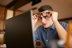 Shocked freelancer hipster man looks to laptop screen and can not believe unpleasant news. Pop-eyed frightened businessman trader raises one's glasses above his eyes. Trader monitoring stock exchange