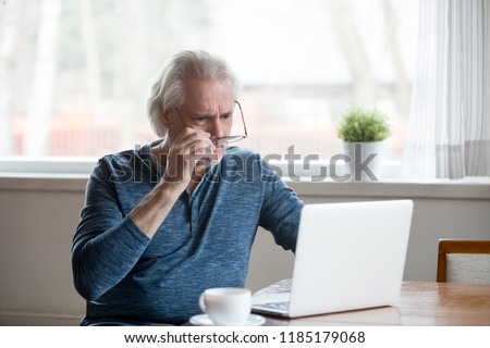Shocked frustrated senior mature man taking off glasses to look at laptop reading shocking online news at home, stressed worried middle aged old male confused by bad email news or computer problem