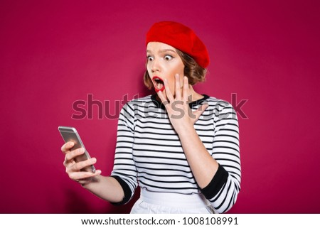 Shocked ginger woman holding cheek while using smartphone over pink background #1008108991