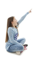 Shocked girl pointing with finger, sitting on floor. Isolated on white background