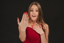 Shocked girl showing proposal ring on her hand wearing dress on grey background