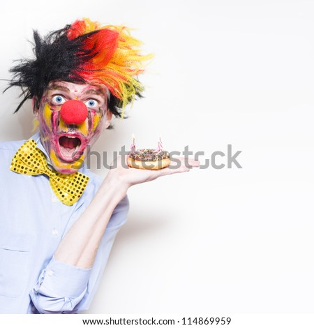 Shocked Happy Birthday Clown Holding Doughnut Party Cake With Two Candles During A Childs Birthday Party On Copy Space Background