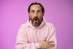 Shocked impressed gossiping caucasian bearded adult 40s man grey hair in pink hoodie gasping fascinated fold lips wow widen eyes astonished hearing interesting thrilling story, purple background