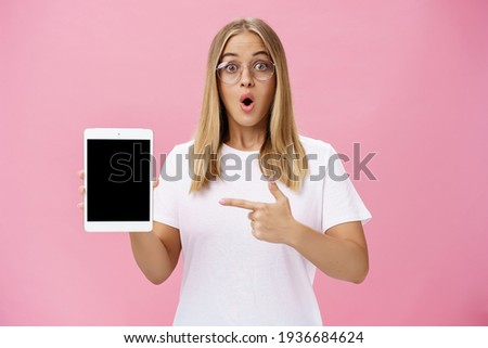Shocked intelligent cute female in glasses and white t-shirt folding lips from amazement in wow sound gasping popping eyes amused holding digital tablet pointing at gadget screen over pink wall Stockfoto ©