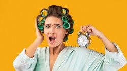 Shocked Lady With Curlers Holding Alarm Clock Being Late For Work Standing On Yellow Studio Background, Looking At Camera. Oversleeping And Deadline, Not In Time Concept. Panorama