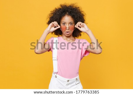 Shocked little african american kid girl 12-13 years old in pink t-shirt eyeglasses isolated on yellow wall background studio portrait. Childhood lifestyle concept. Mock up copy space. Looking camera Stock photo ©