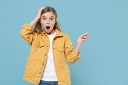 Shocked little blonde kid girl 12-13 years old in yellow jacket isolated on blue background studio. Childhood lifestyle concept. Mock up copy space. Pointing index fingers aside, put hand on head.