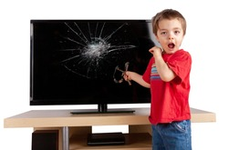 Shocked little boy holding a slingshot standing in front of a TV with broken screen. Home insurance concept. Studio shot isolated on white background.