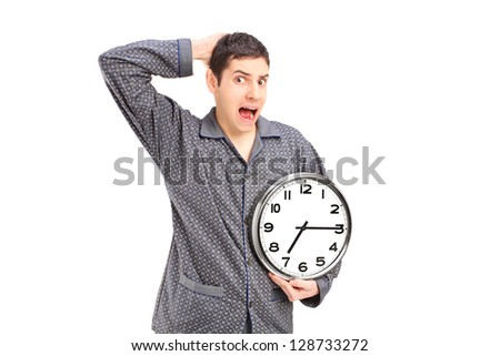Shocked male in pijamas holding an alarm clock isolated on white background