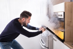Shocked Man Looking At Burnt Cookies With Smoke Coming From Oven
