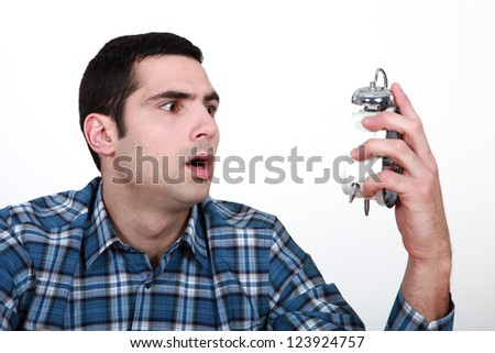 Shocked man with an alarm clock
