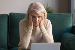 Shocked middle aged mature woman feeling stressed reading unbelievable online news, surprised senior old lady looking at laptop amazed by unexpected stuck computer problem sit on sofa at home