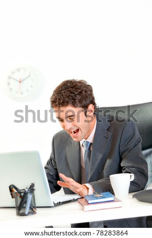 Shocked modern businessman sitting at office desk and discontentedly yelling on laptop