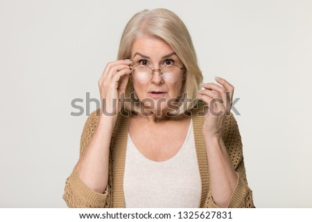 Shocked old mature woman in disbelief lowering glasses looking at camera, surprised stunned amazed senior mid aged lady grandma peering feeling astonished isolated on grey white studio background
