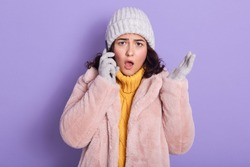 Shocked outraged young woman standing isolated over lilac background in studio, gossiping over mobile phone, putting her smartphone close to ear, opening her mouth widely. Breaking news concept.