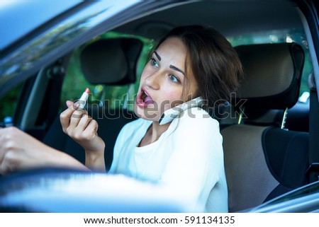 shocked pretty girl with lipstick and phone while driving #591134135